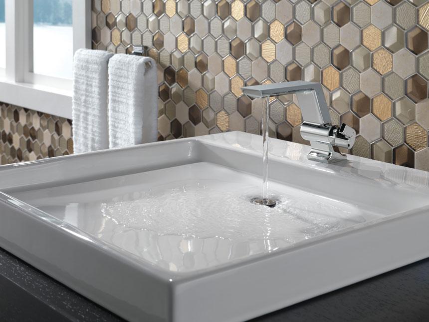 Delta Chrome Pivotal Single Hole Lavatory Faucet With Hexagonal Tile Backsplash and Above Counter Sink